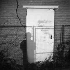 Gaining Entrance (Chuck Baker) Tags: alternative analog abandoned architecture blackandwhite building blackwhite believe camera darkroom door doors film gelderland graffiti holland industrial industry nijmegen lomography lomo lens light monochrome nederland netherlands notechography old photography photograph plastic peace rangefinder surreal toy viewfinder wall z