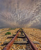Tracks to Nowhere (adrians_art) Tags: dungeness beach coast shore pebbles railways tracks trains lines patterns sky cloud rusty iron red yellow gold evening orange amber light dark silhouettes shadows uk england kent