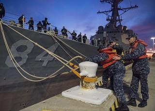 Sailors remove mooring lines as destroyer leaves Norfolk.