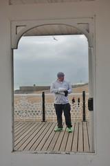 Pier People (II) (Henry Hemming) Tags: people street photography brighton pier glass window frame view seaside sea england portrait man chips leisure