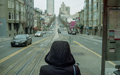 Ayaka waits at the trolley stop, San Francisco (carlfieler) Tags: sanfrancisco cityscape landscape skyline urban city antiportrait trolley infrascructure publictransit 35mmfilm canonet canon analog canonet28 kodak kodakgold kodakgold200 kodak200 c41