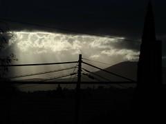 Shining through... (isaacullah) Tags: power lines clouds sun rays mountains suburban drama dramatic mono monochrome black white sepia low key sillhouette