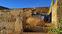 Tumbleweed among the ruins - abandoned commercial building, Lowell, Bisbee, Arizona. (edk7) Tags: nikond3200 edk7 2013 us usa arizona cochisecounty bisbee lowell ghosttown heritagedistrict old vintage classic architecture building oldstructure city cityscape urban store vacant abandoned ruin stucco adobe sky tumbleweed ruins commercial crusty