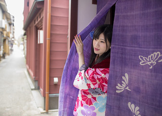 Beautiful woman in kimono going out from shop