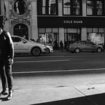 A Man in a Leather Jacket Standing Outside of a Shadow thumbnail