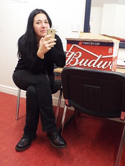 Budweiser..... Don't even think about trying ... ha ha (sean and nina) Tags: nina serb bud budweiser beer box red table mobile phone electronic device camera long dark brunette hair seated sitting chair carpet black jeand clothes clothing dm boots doc martens indoors inside derry touts concert green room woman female girl lady girlfriend fiancee wife married happy expression eyes brown pink lips face portrait unposed hands neck throat beauty beautiful gorgeous stunning charm charming cute smile smiling