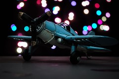 Miniature airplane (DorianTib) Tags: airplane dreams hopes light sparks glow miniature toy blue colorful dark black propeller old wings military christmas childhood flying bokeh night indoor