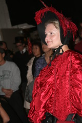 Dickens Christmas: Woman in a Red Costume (shaire productions) Tags: victorian edwardian costume style image imagery event xmas christmas fair festival sf sanfrancisco girl woman red bonnet shawl beauty smiling candid people dickenschristmas portrait