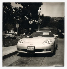 Angelyne's 'Vette (tobysx70) Tags: impossible project tip polaroid amigo instant bw blackandwhite film for 600 type cameras impossaroid angelyne's 'vette beachwood drive canyon village hollywood hills los angeles la california ca angelyne chevrolet corvette vette car automobile angelnn icon rent license plate us usa flag stars stripes trees toby hancock photography