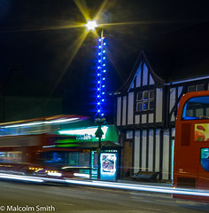 Quicker By Bus (M C Smith) Tags: bus buses lighttrails lights christmas red blue christmaslights bench pentax k3 shops movement speed dark star night advert poster black letters green