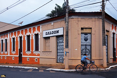 Saloon (Otacílio Rodrigues) Tags: rua bicicleta street prédio esquina corner mulher woman urban candid movimento movement placa casarão house bighouse montecarmelo brasil oro streetphoto barbearia barbershop supershot postes lampposts