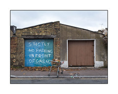 """Everybody Say """"R"""", East London, England. (Joseph O'Malley64) Tags: garages backgardengarages outbuildings garagedoors eastlondon eastend london england uk britain british greatbritain brickwork cement pointing pitchedroofs capstones locks padlock padlocked secured houses victorianhouses victorianstructures tvaerials redundantanaloguetvaerials bushes loftconversion shoppingtrolley dumpedshoppingtrolley cardboardboxes litter rubbish fallenleaves sign signage droppedkerb ramp compositekerbing tarmac doubleyellowlines noparkingatanytime parkingrestrictions paint handpainted handpaintedsign subsidence subsiding urban urbanlandscape fujix x100t accuracyprecision"""