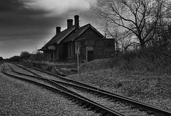 The Train Is Late (tcees) Tags: lyddrailwaystation lydd romneymarsh kent platform railwaytrack nikon d5200 1855mm bw mono monochrome blackandwhite abandoned ruin sky clouds grass railwaylines rails railway sleepers tree building chimney windows roof gravel allfreepicturesjanuary2018challenge