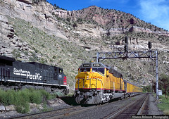 A Meet at Utah Railway Junction by jamesbelmont - A trio of Southern Pacific AC4400CW units are stopped at Utah Railway Junction while a Union Pacific Salt Lake City to Grand Junction officer's special rumbles by on the morning of Aug. 13, 1997.