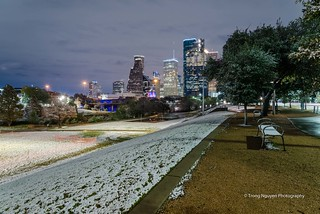 Empty bench and Downtown Houston at  night with big and fluffy snowflakes