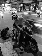 Roadside service (gergelytakacs) Tags: man rider bike scooter night road crossing tyre tyres crosswalk blur helmet motor motorbike broken honda mirror shorts flipflops vietnam việtnam hồchíminh hochiminh saigon thànhphố sàigòn asia asian vietnamese fareast southeastasia streetphotography street streetphoto unposed urban urbanphoto city streetscape urbanphotography streetphotographer public space candid stranger documentary people streets documenting photo photography rue calle strada ulica utcafotó strasenfotografie улица רחוב black white monochrome blackandwhite bw blanco negro noir blanc x20 fujifilm fuji compact zoom xseries