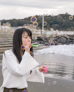 High school girl playing with soap bubbles on beach