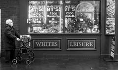 leisure (Chilanga Cement) Tags: fuji fujix100f x100f xseries street streetphotography bw blackandwhite monochrome southport christmas arcade leisure lady shopping shopper window amusements trolley