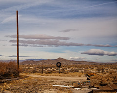 The desert is a place without expectation (Maureen Bond) Tags: ca maureenbond desert mojave abandoned clouds sky tire pole brush trash 52in2018 strange