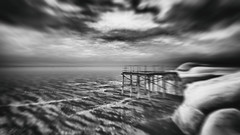 Too Bright to Even See the Sun (Gianmario Masala [inworld]) Tags: photoshop blur blurry mono monochrome landscape north gianmariomasala blackandwhite motion ocean sea reef stones misty grain highandlowkey shadows waves beach pier wind sky clouds
