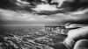 Too Bright to Even See the Sun (Gianmario Masala [inworld]) Tags: photoshop blur blurry mono monochrome landscape north gianmariomasala blackandwhite motion ocean sea reef stones misty grain highandlowkey shadows waves beach pier wind sky clouds
