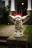 Merry Christmas! (sebboh) Tags: carlzeisscontaxg45mmf2planar sonya7kolariut zeissrokkorfrankenlens christmas gargoyle dog santa hat portland oregon pdx bokeh