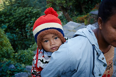 Nepali mother carrying her baby, Landruk, Annapurna massif, Nepal (Alex_Saurel) Tags: asia culture green portray bonnetpéruvien photoreport lifescene porter vert asian day annapurnabasecamptrek reportage redbun scènedevie travel portraiture bébé people 35mmprint vegetation nepal photospecs carrying mère redbonnet femme portrait peruvianbonnet abctrek imagetype motif woman bonnetrouge child nature lifestyles asie photojournalism scans stockcategories peruvianhat baby bun annapurnaconservationarea pattern photoreportage smallchild time portage sony50mmf14sal50f14