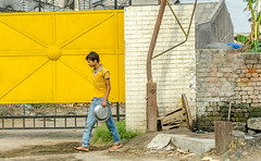 Yellow shirt at the yellow gate (Pejasar) Tags: youthboy teen youngman male yellowshirt yellowgate metalpan barefoot walking streetcandid newdelhi india