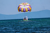 Summer Fun (vickieklinkhammer) Tags: water parachute sky beach nature floating outdoors vacation adventure boat parasailing balloon outdoor sphere travel windsports object coast summer leisure surfacewatersports blue recreation body man airsports air leisureactivities towedwatersport colorful riding transportation wind vessel yellow watercraft lake flying gliding landscape umbrella clear people outside august morning sunshine purple waves mountainrange