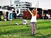 245. FAIR: Hula Hooping Queen (Meili-PP Hua 2) Tags: fair grass field park gypsy streetphotography girl woman people sports hulahoop picnic mlpphlandscape buildings green houses tents caravans urban mlpphurban mlpphcity city mlpphstreet
