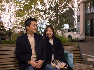 Young couple sitting on bench under Christmas lights