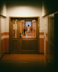 ... there she goes ... (Thomas Listl) Tags: thomaslistl color door glass indoor people woman hospital patient orange vanishingpoint light budapest hungary mood atmosphere dark vsco