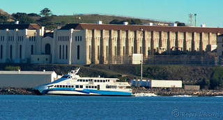 Commuter Ferry Passing Freely Beneath the Drab and Dreary Walls of San Quentin Prison