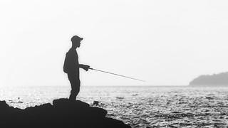 Silhouette Of Man Fishing On Beach.
