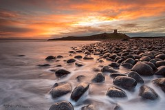 Dunstanburgh Dawn (Pureo) Tags: amateur beach canon canon6d clouds coast castle dawn dunstanburgh exposure england flowing flow goldenhour glow landscape northeast northsea northumberland northeastengland pebbles rocks seascape sky sunrise sea water waterscape waves deathrocks