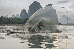 The cast net (tmeallen) Tags: cormorantfisherman cast net fishing circularnet sunset limestone karstmountains throwingnet ancientpractice dyingculture reflections liriver lijiang xingpingfishingvillage guilin guangxiprovince china