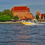 Wat Sanam Nuea with boat passing on the Chao Phraya river opposite Koh Kret, Thailand thumbnail