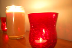 Candles Aglow. (dccradio) Tags: lumberton nc northcarolina robesoncounty indoors inside candle candles burning illuminated flame redcandleholder candleholder tealightcandle jarcandle wall fire nikon d40 dslr tealight red light candlelight blur blurred blurry