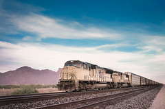 Freight train in Arizona desert landscape (evolutionlabs) Tags: trina arizona cargo classic clouds container crossing delivery desert destination diesel engine freight haul horizon industrial industry journey line locomotive metal motion mountain movement new perspective power powerful rail railroad railway shipping sky speed sunset supplies track train transit transport transportation travel usa west wheels white wild wilderness unitedstatesofamerica