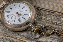Vintage Pocket Watch On Wood (AudioClassic) Tags: time vintage watch antique old retro metal pocket clock minute aged hour history chain background abstract ancient elegant concept obsolete grunge wood bronze wooden classic dirty mechanic timepiece table textured timepassing silver macro pocketwatch numbers brass instrument accessory mechanism dial past object metallic design nostalgia symbol artwork fashion decoration mechanical jewellery