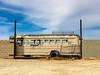 End of the Trail (Maureen Bond) Tags: ca maureenbond bus wall locked broken glass windows iphone tires fence desert