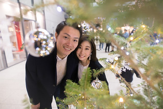 Young wife and husband looking at camera through Christmas tree