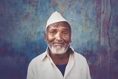 Portrait of a Marathi Man in Gandhi Topi (Gandhimonkey) Tags: portrait old smile indian asia outdoor travel nikon gandhi topi blue