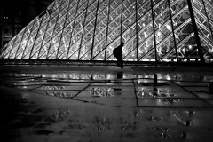 Along the floodlit pyramid (pascalcolin1) Tags: paris louvre pyramide pyramid homme man nuit night illuminé floodlit pluie rain reflets reflection lumières lights photoderue streetview urbanarte noiretblanc blackandwhite photopascalcolin canon canon50mm 50mm