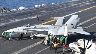 Sailors push jet on flight deck of aircraft carrier.