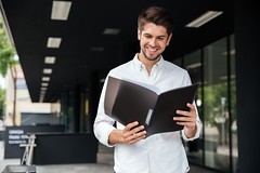 Happy businessman standing and looking through documents in folder (TranslationAgency) Tags: folder report plan opened documents reading business architecture assistant boss building businessman caucasian central cheerful clever commercial confident consultant content expertise financial fresh guy happy look male man manager modern outdoor positive profession reliability satisfied smile solution standing think worker