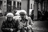 The importance of wearing a hat (damar47) Tags: streetphotography streetstyle streetlife blackwhite biancoenero blackandwhite two ladies oldladies azdore da40mmf28xs pentax pentaxart k30 monochromatic monochrome bologna italy italia portici porch candidportrait walking walk chatting hat hats citylife urban
