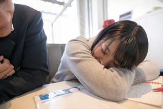 High school girl sleeping during studying in cafe