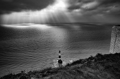 The Breakthrough (Lloyd Austin) Tags: rocks cliffs nikon d5100 sigma1750mm lighthouse water coastline coastal shoreline ocean seascape sea light sunrays sky overcast storm clouds cloudscape monochrome mono bnw blackandwhite bw moody atmospheric dramatic stormy england eastsussex beachyhead thebreakthrough