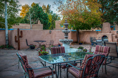 Rear Courtyard of Casa Benavides (donnieking1811) Tags: newmexico taos inn outdoors courtyard adobe walls tables chairs fountain firepit trees flowers cactus painting art canon 60d lightroom photomatixpro
